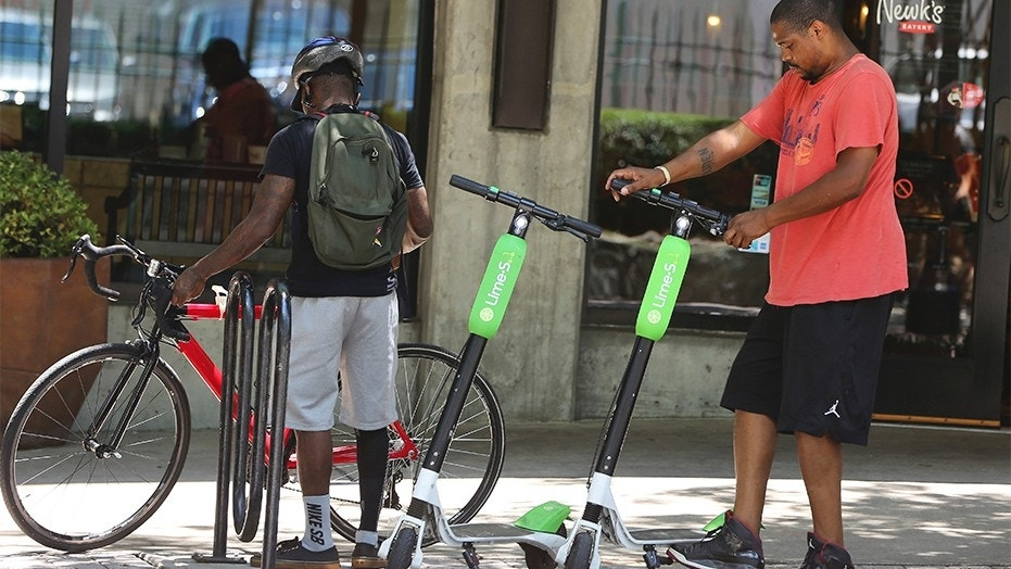 FILE --  A man parks his rented dockless scooter outside of a restaurant in Atlanta.