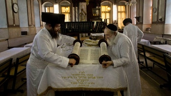 Sept. 13, 2013 - Ultra-Orthodox Jewish men roll a torah scroll ahead of Yom Kippur, in Jerusalem. Yom Kippur is Judaism's day of atonement, when devout Jews ask God to forgive them for their transgressions and refrain from eating and drinking, attending intense prayer services in synagogues.