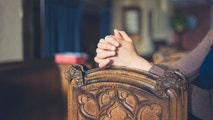 Close up on the folded hands of a woman praying in church