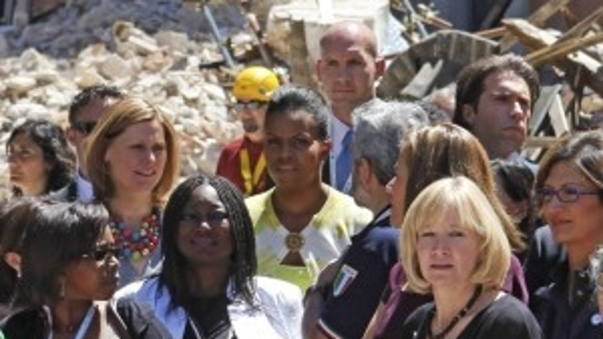 First lady Michelle Obama, center, tours earthquake damage with Sarah Brown, wife of British Prime Minister Gordon Brown, second from top left,  Juliana Olabintan Nwanze, wife of International Fund for Agricultural Development (IFAD) president Kanayo Nwanze, second from bottom left, Laureen Harper, wife of Canadian Prime Minister Stephen Harper, second from right foreground, and others on the sidelines of the G8 Summit in L'Aquila, Italy, Thursday, July 9, 2009. (AP Photo/Charles Dharapak)