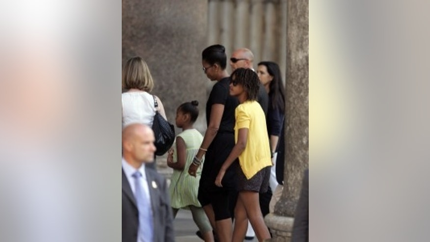 US First Lady Michelle Obama, in black dress at center, between her daughters Malia, at right in yellow top, and Sasha, in green dress, walk past towering stone columns as they arrive for a visit of Rome's ancient Pantheon, Thursday, July 9, 2009. After her return to Rome from L'Aquila, central Italy, Michelle Obama and her daughters, took a private, 30-minute tour of the Pantheon, the well-preserved ancient Roman monument with massive concrete dome in the heart of Rome. Obama and other first spouses toured the center of L'Aquila earlier Thursday to see the destruction wrought by an earthquake in the Italian city hosting world leaders this week for the Group of Eight summit. (AP Photo/Riccardo De Luca)