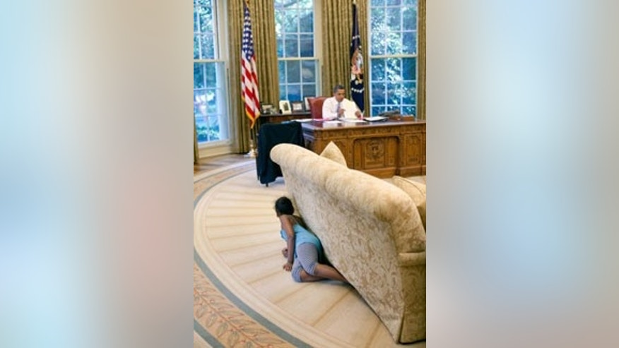 President Barack Obama's daughter Sasha hides behind the sofa as she sneaks up on him at the end of the day in the Oval Office, Aug. 5, 2009.
