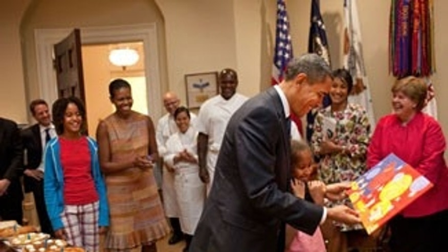 President Barack Obama, with daughter Sasha, looks at the card given to him during a birthday party with his staff in the Roosevelt Room of the White House, August 4, 2009. Daughter Malia nd First Lady Michelle Obama look on at left. (Official White House Photo by Pete Souza)