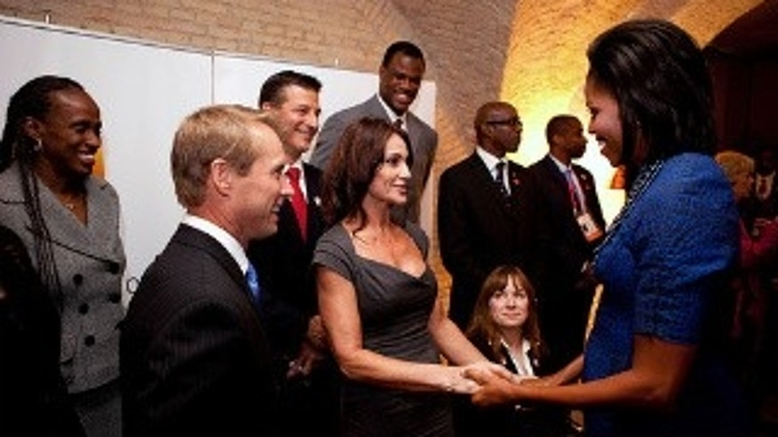 First Lady Michelle Obama greets gymnast Nadia Comaneci, her husband gymnast Bart Connor, left, Paralympic athlete Linda Mastandrea, center-right , and other former Olympians before the Chicago 2016 Dinner in Copenhagen, Denmark.From left in the background; athletes Jackie Joyner-Kersee, Bob Berland, David Robinson, Dr. Edwin Moses and Mike Conley. (WH Photo)