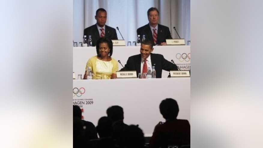 U.S. President Barack Obama and first lady Michelle Obama attend the 121st International Olympic Committee Session in Copenhagen, Denmark, Friday, Oct. 2, 2009. (AP Photo/Gerald Herbert)