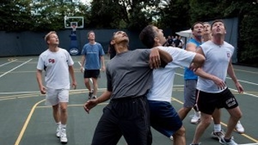 President Barack Obama, along with Cabinet Secretaries and Members of Congress, watch a shot during a basketball game on the White House court, Oct. 8, 2009.   (Official White House Photo by Pete Souza)