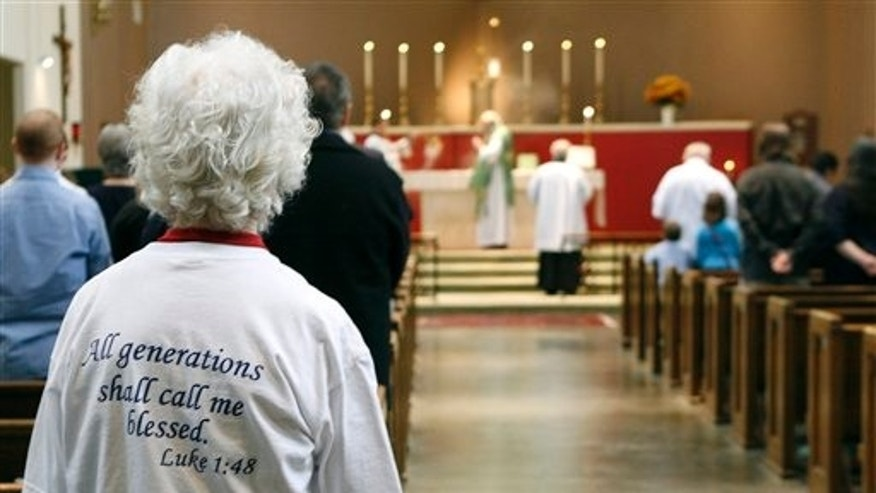 In this Sunday, Oct. 25, 2009 photo, Lavon Ferrell, left front, attends Sunday Mass at Saint Mary the Virgin Catholic Church  in Arlington, Texas. The conservative church became a Roman Catholic church in 1994 after it left the Episcopal Church. (AP Photo/Amy Gutierrez)