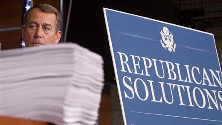 In this Oct. 29, 2009 file photo House Minority Leader John Boehner of Ohio stands behind a copy of the Democrat's version of the health care bill during a news conference on Capitol Hill in Washington.(AP)