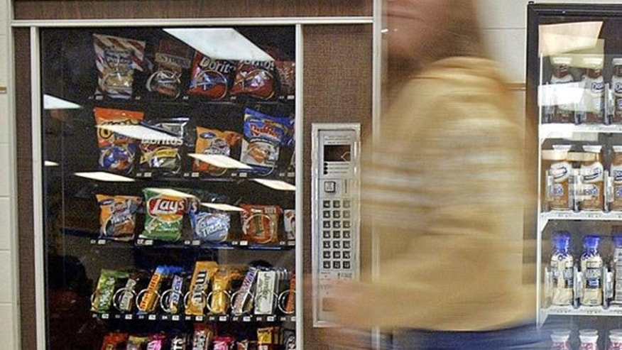 A student is shown here walking past vending machines in a Wisconsin high school. (AP Photo)