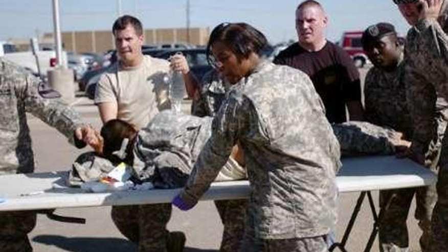 Army first responders use a table as a stretcher to transport a wounded soldier to an ambulance at Fort Hood Nov. 5. (Reuters Photo)