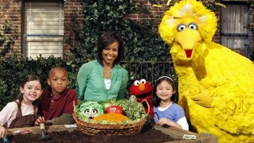 "This May 5, 2009 photo released by Sesame Workshop shows first lady Michelle Obama, third from left, with Big Bird, Elmo, Muppets & cast in ""Michelle Obama Plants A Garden"" in Astoria, N.Y. Mrs. Obama appears on ""Sesame Street"" Tuesday, Nov. 10, 2009, and recently taped an episode of ""Iron Chef America,"" just two of the varied platforms she's been using lately to get her healthy-eating message out to the masses. (AP Photo/Sesame Workshop, Richard Termine)"