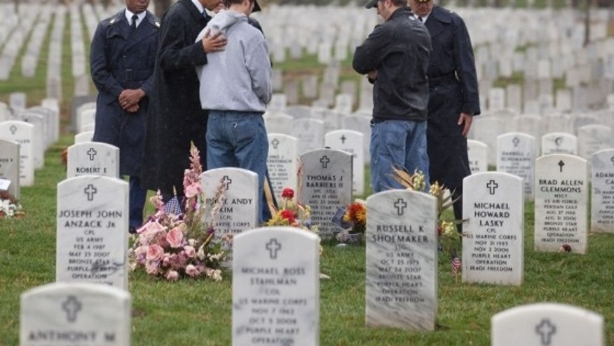 President Barack Obama, second from left, and Gen. Karl Horst, right, stop to talk with visitors among the graves of soldiers from the Iraq and Afghan conflicts in Section 60 of Arlington National Cemetery, Nov. 11, 2009. (Official White House Photo by Samantha Appleton)