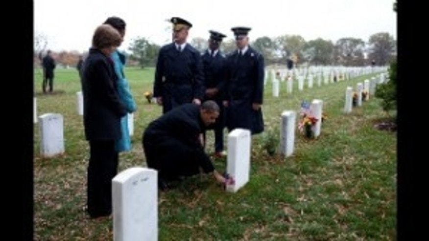 President Obama places a presidential challenge coin at the grave of Specialist Ross McGinnis who was killed in Iraq.