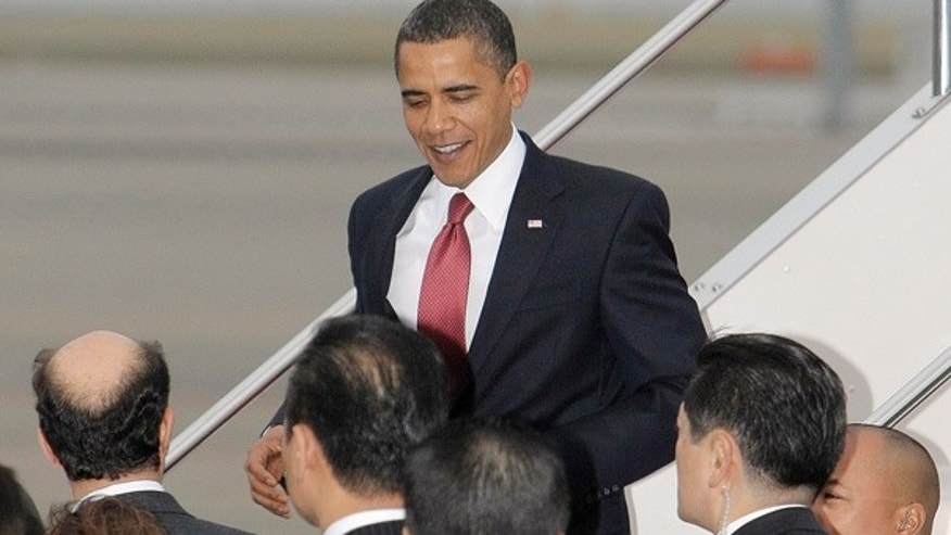 Nov. 13: President Obama walks down the steps upon his arrival on Air Force One at Haneda airport in Tokyo, Japan. (AP)