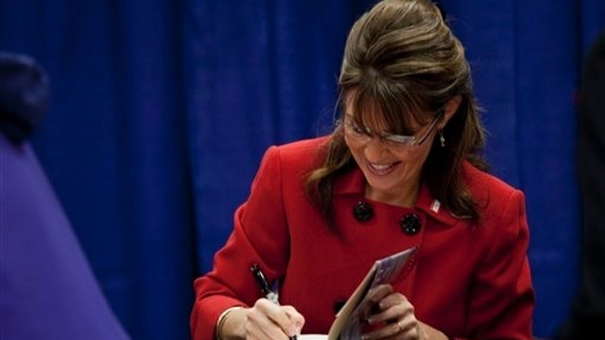 Sarah Palin signs her autograph at Barnes and Nobles during the first stop of her book tour in Grand Rapids, Mich. on Wednesday, Nov. 18, 2009. (AP Photo/Adam Bird)