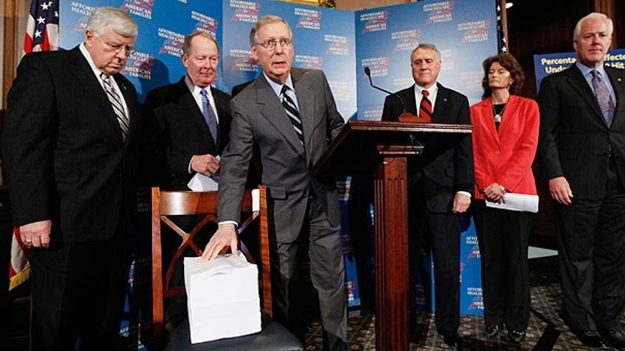 Nov. 20: Senate Minority Leader Mitch McConnell of Ky., center, is flanked by other Republicans as he shows a copy of the Democratic health care reform bill on Capitol Hill. (AP)