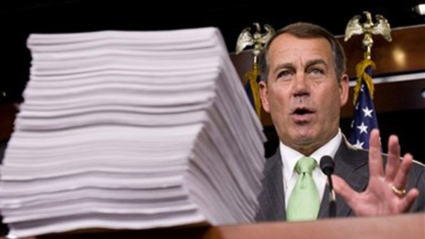 House Minority Leader John Boehner stands behind a copy of the health care bill Oct. 29 on Capitol Hill. (AP Photo)