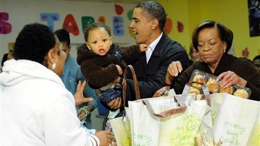 President Obama holds an unidentified child as he stands next to his mother-in-law Marian Robinson as they pack food for Thanksgiving at Martha's Table, a food pantry in Washington, Wednesday, Nov. 25, 2009.(AP)