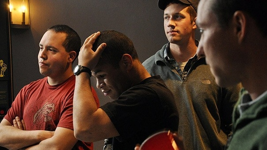 Dec. 1: Spc. Adam Candee, Spc. Kenny Hoggatt, Sgt. Matt Lukasik and Private Sam Michalik react as they watch Obama announce an additional 30,000 troops will be deployed to Afghanistan. (AP)