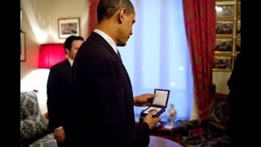 President Obama looks at his Nobel Peace Prize. White House Photo.