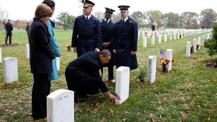 President Barack Obama leaves a presidential coin at the gravesite of 19-year-old Medal of Honor recipient, Specialist Ross McGinnis, who is one of two Medal of Honor recipients memorialized at Arlington Cemetery from the wars in Iraq and Afghanistan. The President was at Arlington Cemetery to give Veterans Day remarks, Nov. 11, 2009. (Official White House Photo by Pete Souza)
