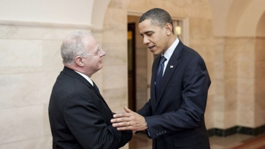 President Barack Obama greets his new White House Cyber Security Chief Howard A. Schmidt in the Cross Hall of the White House, Dec. 17, 2009.
