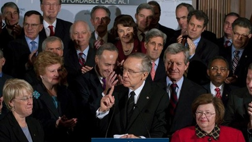Senate Majority Leader Harry Reid of Nev., accompanied by Senate Democrats, speaks during a health care news conference on Capitol Hill, Wednesday, Dec. 23, 2009. (AP)