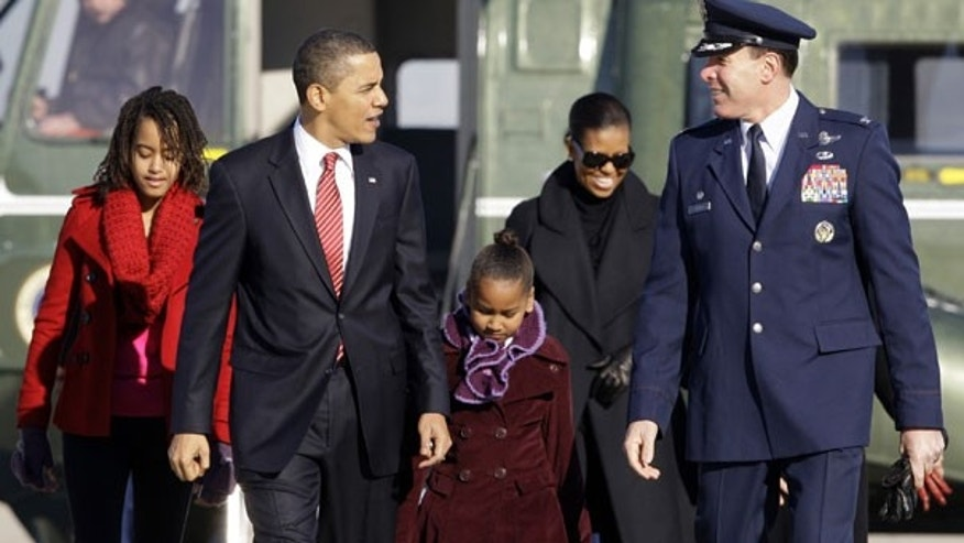 Thursday: President Barack Obama, walks with Malia Obama, 11, left, Sasha Obama 8, and Michelle Obama, with Col. Steven Shepro, to Air Force One at Andrews Air Force Base, Md., on their way to Hawaii for Christmas. (AP Photo)