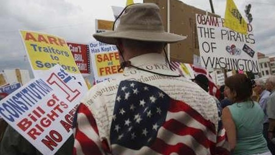 "In this Aug. 31 file photo, ""tea party"" demonstrators hold signs at a protest in Flagstaff, Ariz. (Reuters Photo)"
