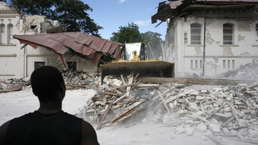 A resident looks at debris being removed from the national palace in Port-au-Prince Jan. 13. (Reuters Photo)