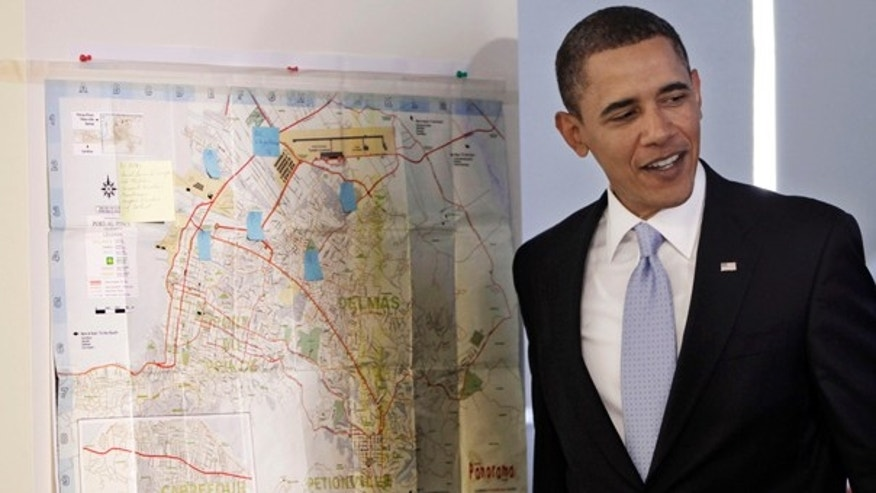 Monday: President Obama stands by a street map of Port-Au-Prince, Haiti, during a visit to the Red Cross Disaster Operation center in Washington. He will deliver his first State of the Union address on Wed., Jan. 27. (AP)