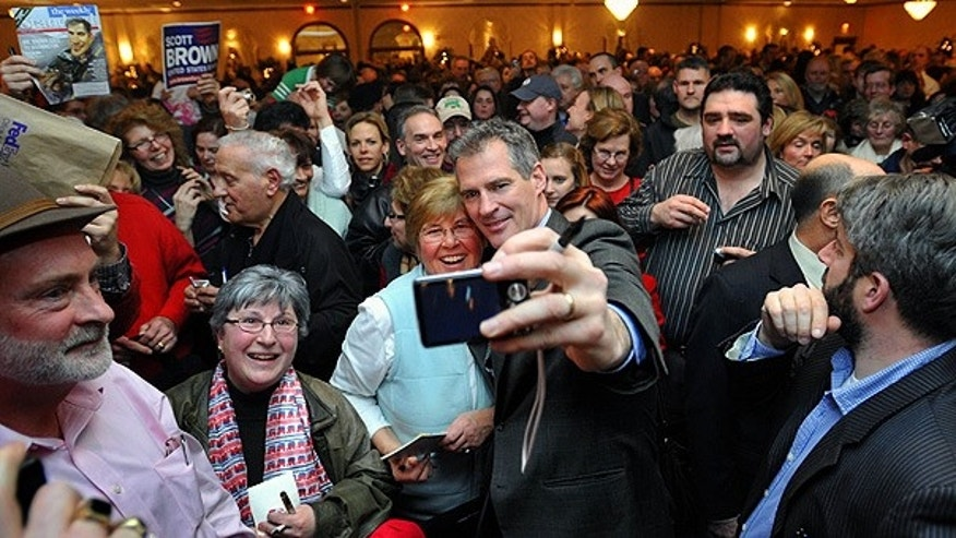 Jan. 31: Republican Sen.-elect Scott Brown, center, snaps a photo with supporters in Foxborough, Mass.