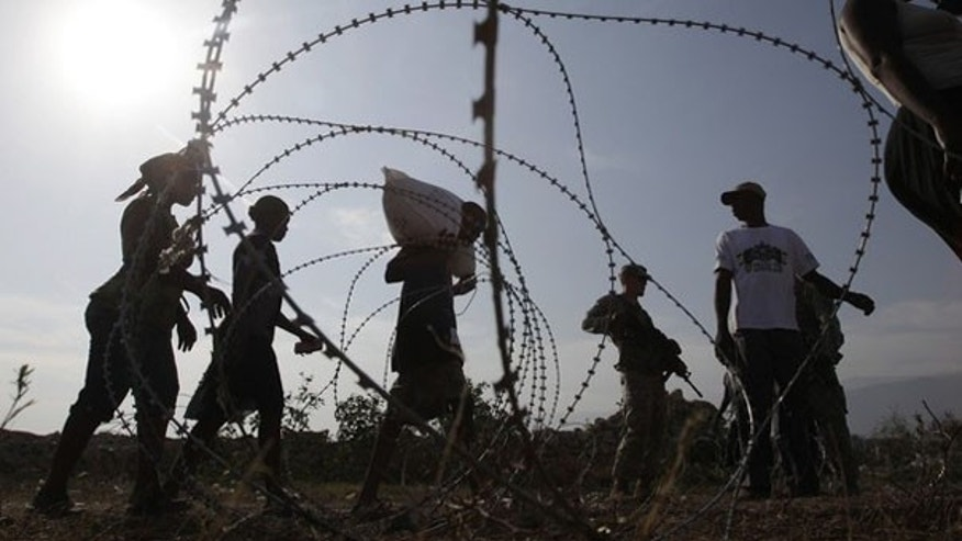 Haitians walk in front of barbed wire during a food distribution in Port-au-Prince Feb. 15. (Reuters Photo)