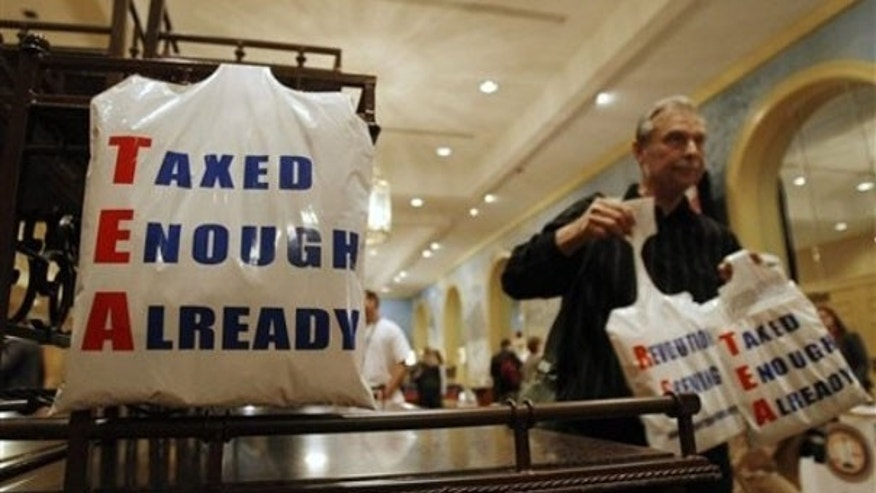 A vendor gives away plastic bags at the National Tea Party convention in Nashville Feb. 5. (AP Photo)