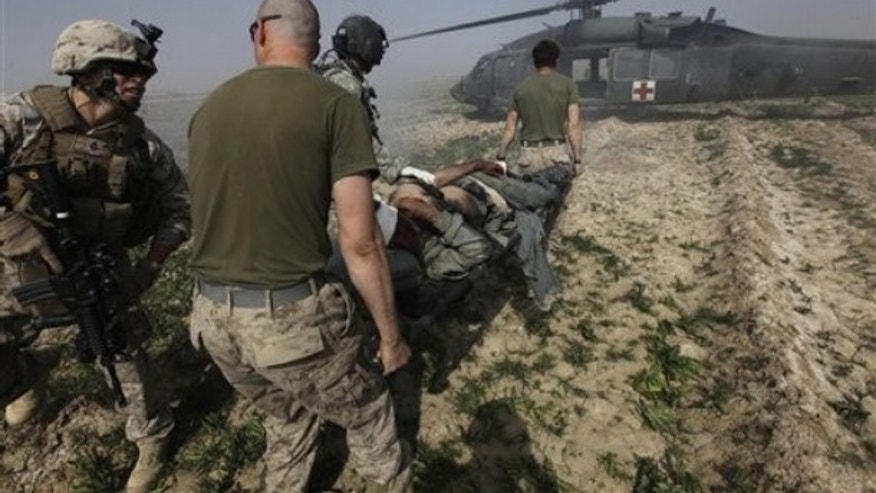 During a medevac mission by the U.S. Army's 82nd Airborne, an Afghan National Army soldier wounded in an IED attack is carried to a waiting helicopter, in Marjah Helmand province, Afghanistan, Feb. 26. (AP Photo)