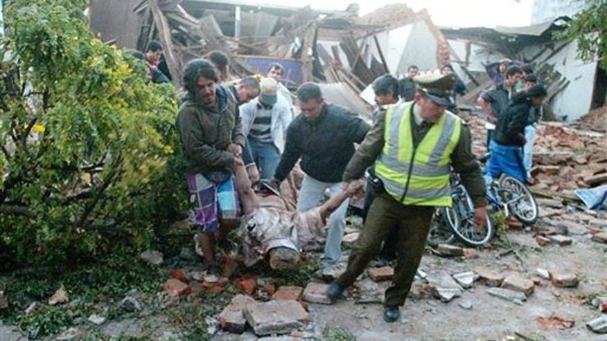 A police officer and residents, carry a body from a destroyed house in Talca, Chile, some 275 kilometers south of Santiago, Saturday, Feb. 27, 2010 after an 8.8-magnitude struck central Chile. (AP)