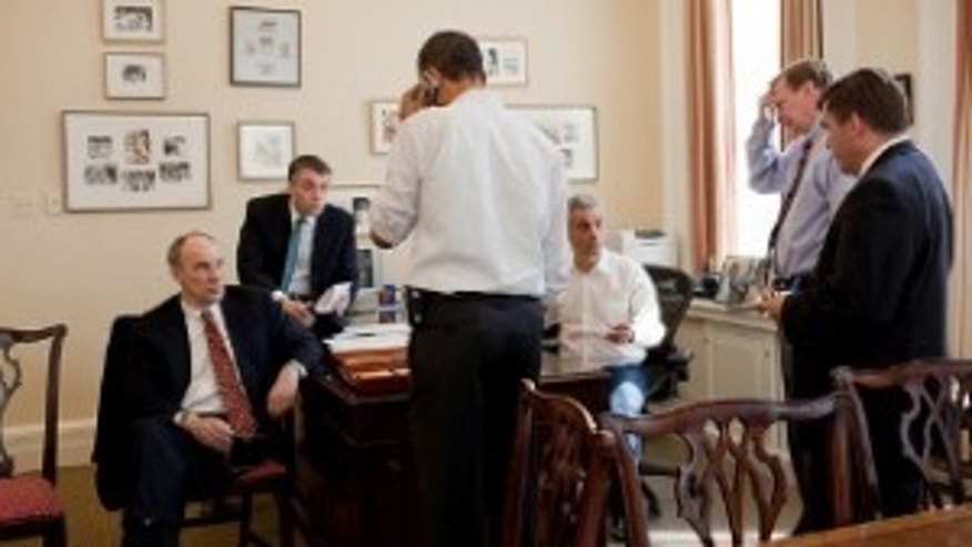 President Barack Obama talks on the phone with a Member of Congress in the Chief of Staff 's office at the White House. From left, aides Phil Schiliro, Sean Sweeney, Rahm Emanuel, Jim Messina, and DanTurton. (Official White House Photo by Pete Souza)
