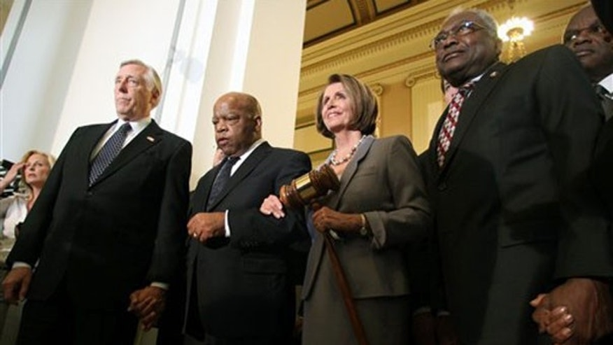 House Speaker Nancy Pelosi holds a large gavel as she emerges from a Democratic caucus meeting with, from left, Reps. Steny Hoyer, John Lewis, and Jim Clyburn on March 21 on Capitol Hill. (AP Photo)