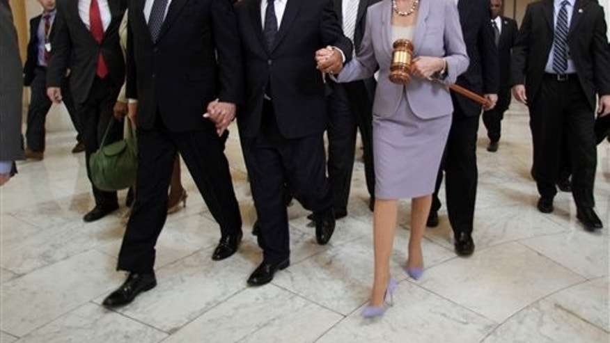Sunday: House Speaker Nancy Pelosi, D-Calif., holds a large gavel as she walks through the Cannon Rotunda after a Democratic Caucus, along with from left, are Reps. Steny Hoyer, D-Md., John Lewis, D-Ga., and John Larson, D-Conn.  (AP Photo)