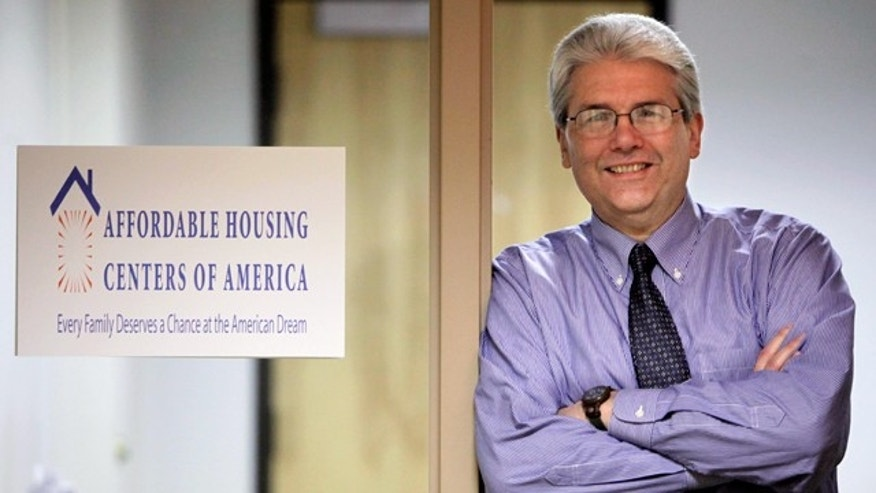 In this photo taken, March 12, 2010, in Chicago, Michael Shea, Executive Director of Affordable Housing Centers of America, formally known as ACORN Housing poses next to the organization's new sign. (AP)
