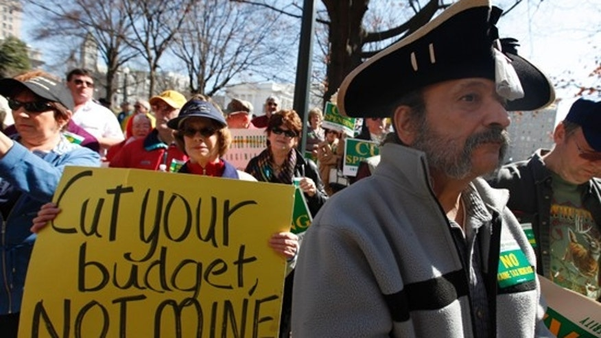 In this March 8, 2010 file photo, Tea Party member Greg Hernandez, of Quicksburg, Va., wearing a tri-corner hat and tea bag, listens to speakers during a rally at the Capitol in Richmond, Va. (AP)