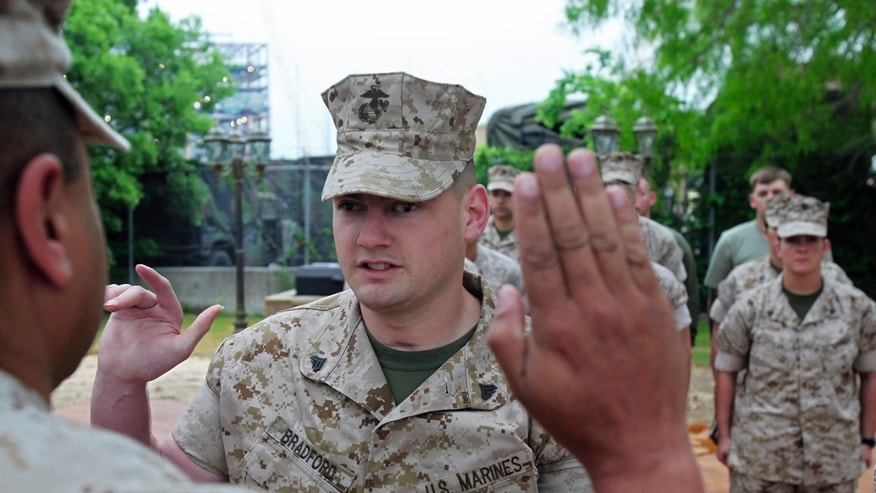Corporal Matthew Bradford is sworn in by Lt. Col. David Barnes as he re-enlists in the Marines at Ft. Sam Houston, Texas April 7, 2010.  Tom Reel/Staff