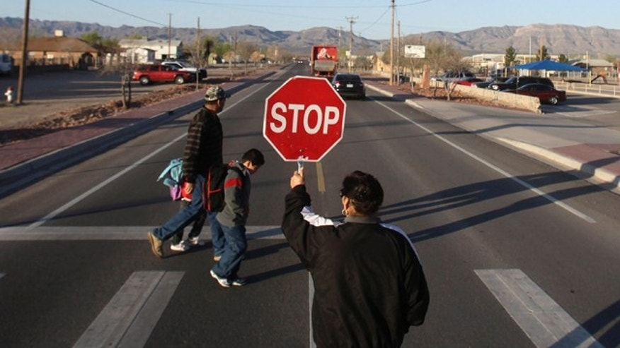 FILE: In this March 26, 2010. photo, a crossing guard holds up a stop sign as a parent and child cross the street to get to school at Fort Hancock, Texas, located about 50 miles southeast of Ciudad Juarez, Mexico, epicenter of a bloody drug war that has sent Mexican families fleeing. (AP)