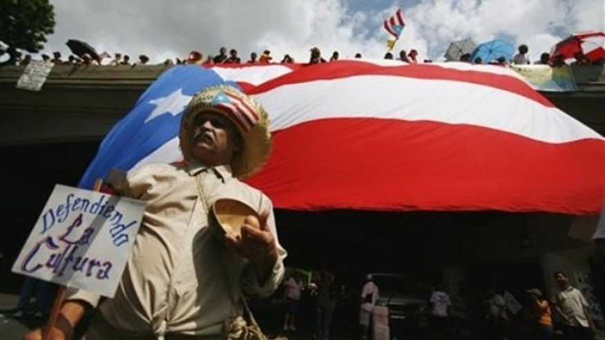 A demonstrator marches under a Puerto Rican flag in San Juan Oct. 15, 2009. (AP Photo)