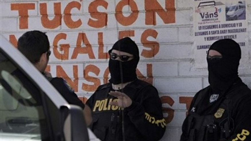 Federal immigration agents stand outside Sergio's Shuttle Thursday, April 15, 2010 in Phoneix. (AP)