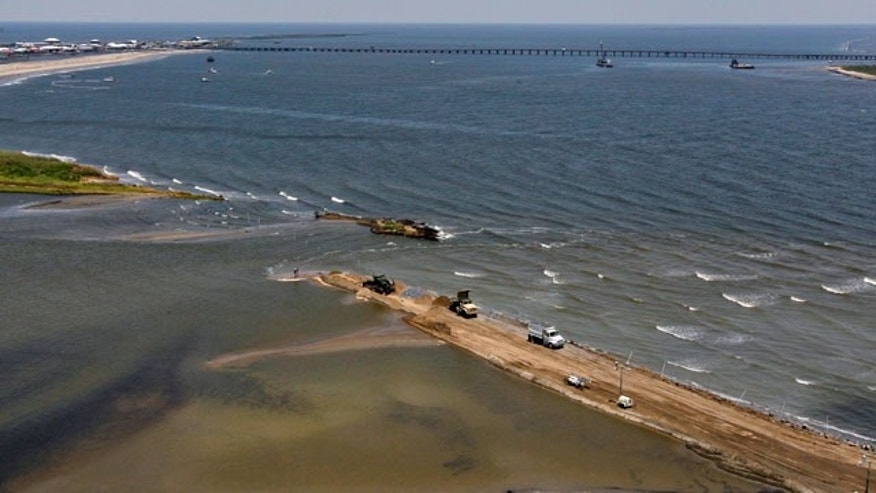 May 10: Louisiana National Guard use dump trucks to dam off part of the marsh on Elmer's Island in Grand Isle, La.