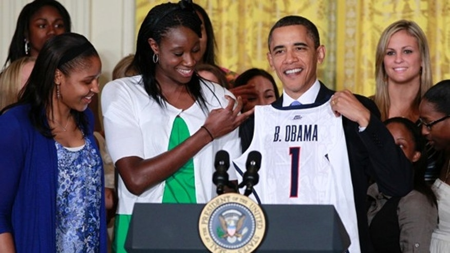 President Obama is presented with a team jersey by Tina Charles, center, and Maya Moore, left, as he honored the 2010 NCAA champion University of Connecticut women's basketball team in the East Room of the White House in Washington, Monday, May 17, 2010. (AP)