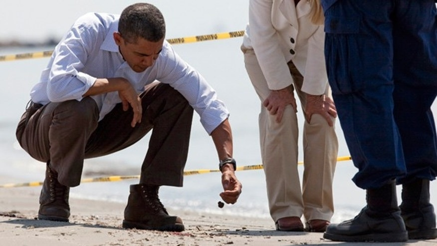 """May 28: President Obama picks up a """"tar ball"""" during a tour of areas impacted by the Gulf Coast oil spill in Port Fourchon, La. He returns to the region on Monday."""