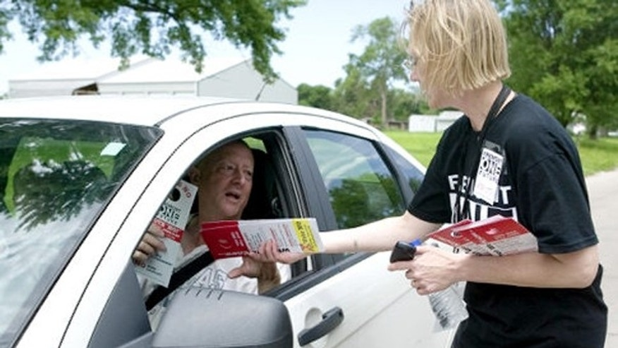 Activist Kristin Olstrom hands out material in opposition to a proposed law in Fremont, Neb., that would impose new restrictions on illegal immigrants. (AP Photo)