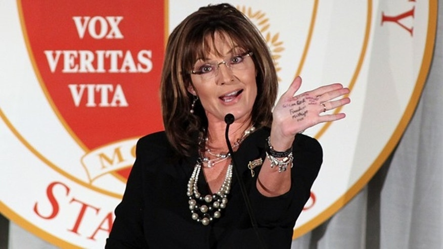 June 25: Calling it a 'poor man's teleprompter' former Republican vice presidential candidate Sarah Palin holds out her palm to show the notes on it while speaking at a fundraising dinner at California State University, Stanislaus. (AP)